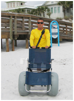 Lifeguard Justin Cook demonstrates one of the new wheelchairs. Lori Ceier/WaltonOutdoors.com