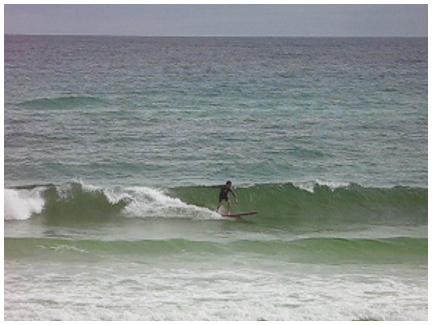 A surfer at Blue Mountain Beach takes advantage of Claudettes chest high waves.