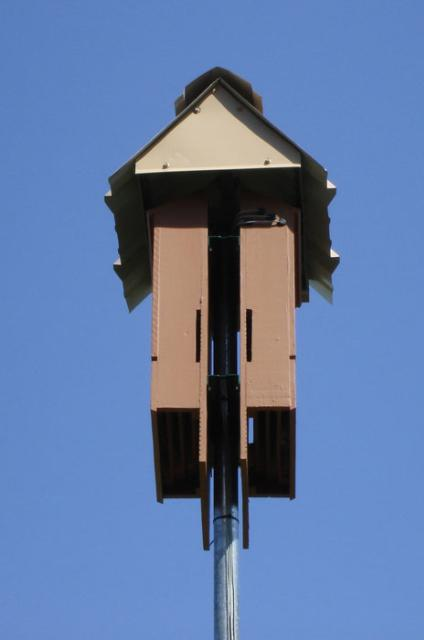 Two 4-chamber bat houses mounted back-to-back on a pole and covered with a metal roof provide roosting habitat for bats. Photo courtesy Escambia County Extension Office