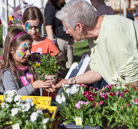 Master Gardener Snookie Parrish helps children plant native flowers. Photo courtesy Shelley Swanger